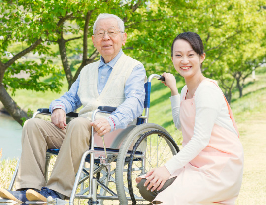 elderly man in a wheelchair with his caregiver